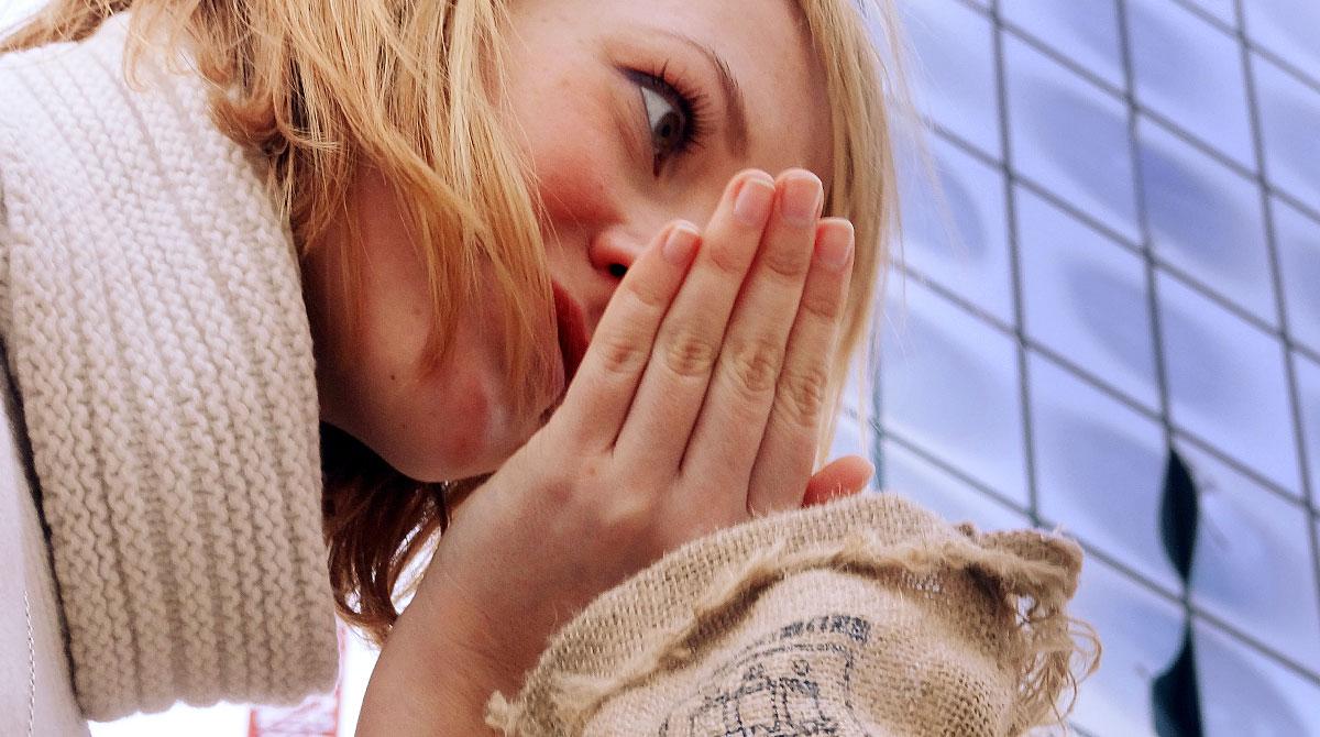 Frau vor der Elbphilharmonie die an einem Kaffeesack riecht