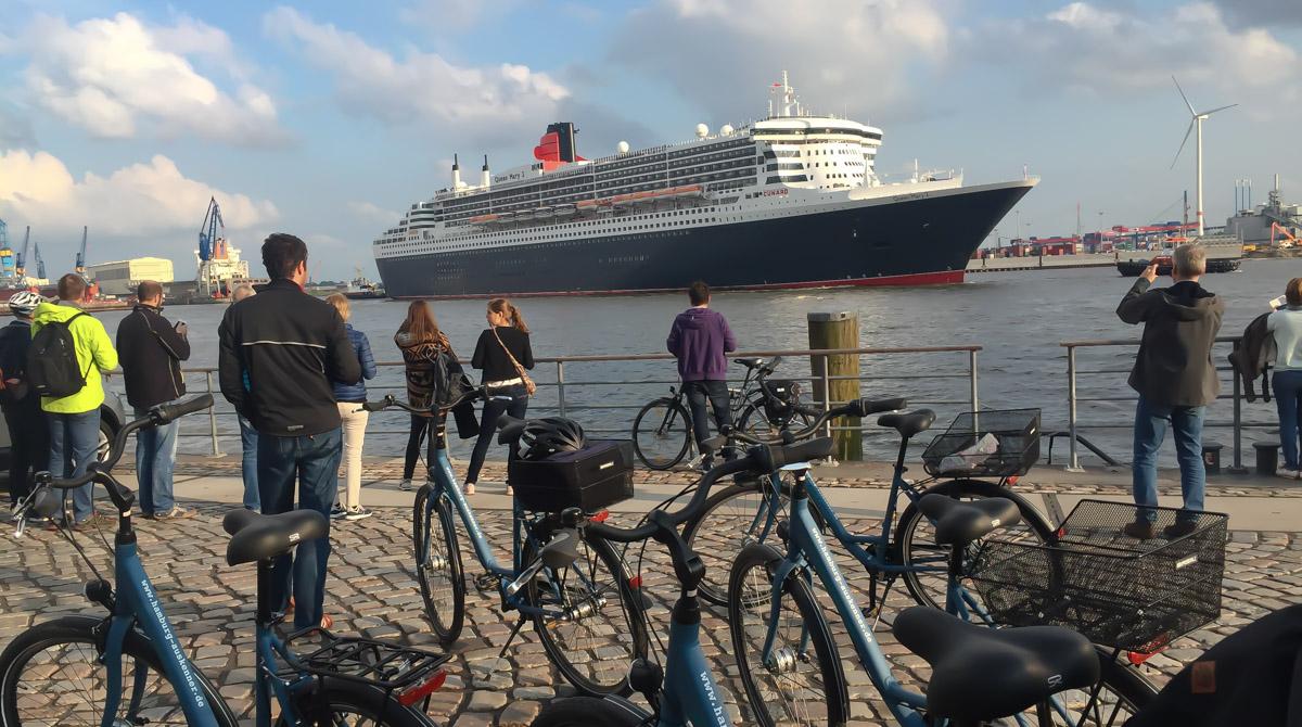 Fahrradtour am Fischmarkt Hamburg schaut auf das Kreuzfahrtschiff Queen Mary 2