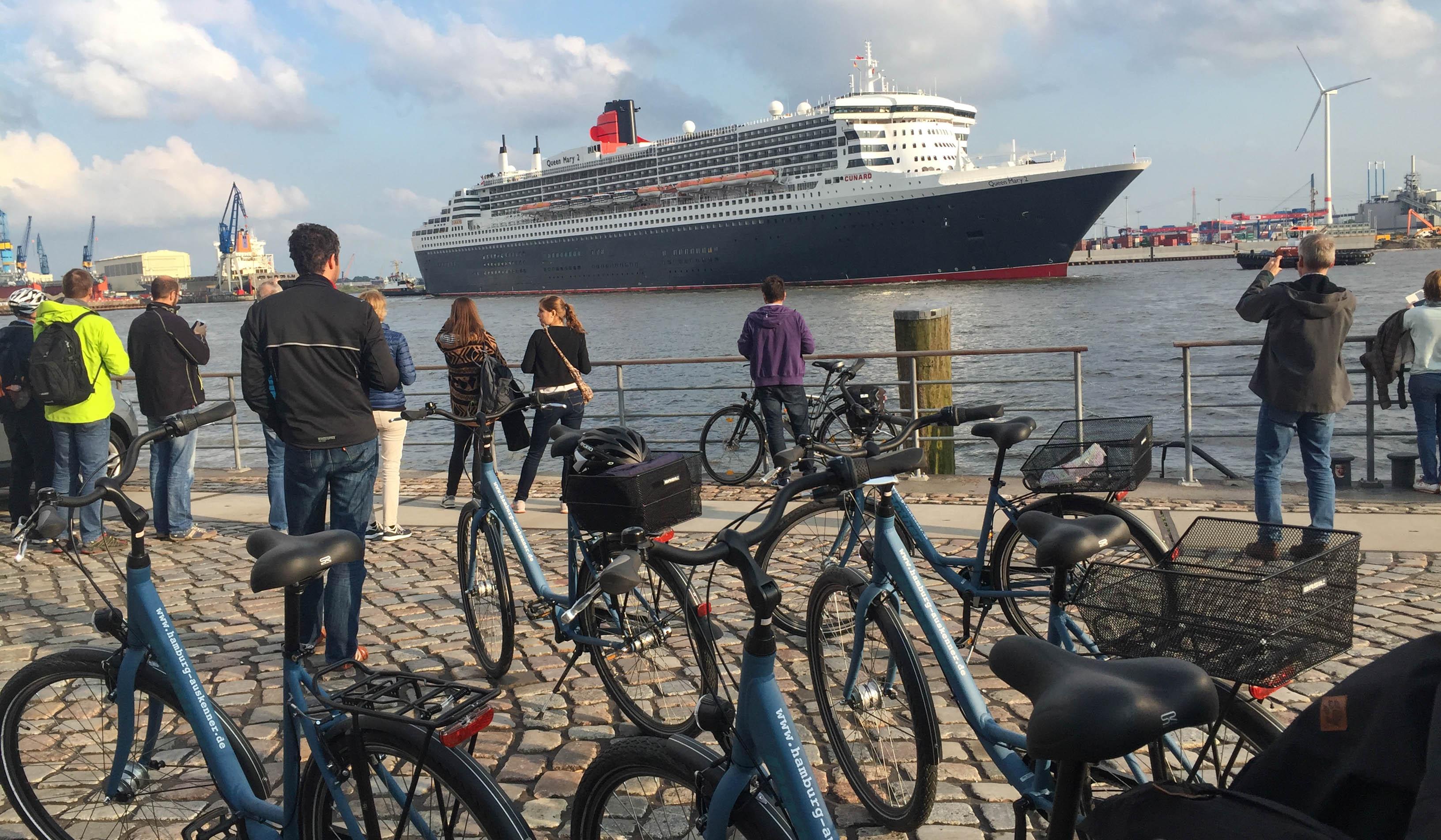 Geführte Fahrradtour als Incentive am Hamburger Fischmarkt. Die Gruppe steht vor den Fahrrädern und schaut auf die auslaufende Queen Mary 2.